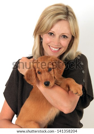 Happy woman holding a Golden Retriever puppy. - stock photo