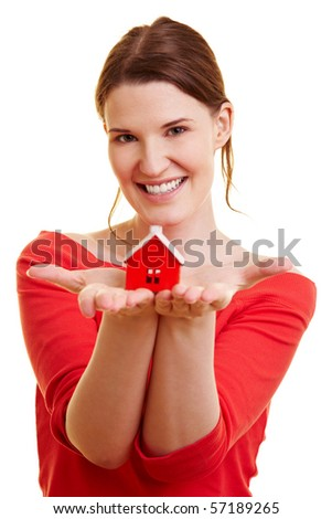Happy woman holding a little red house in her hands - stock photo