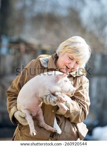 happy woman holding a newborn piglet,domestic animal breeding - stock photo