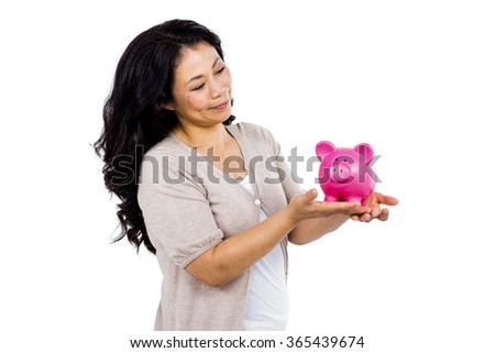 Happy woman holding a pink piggy bank