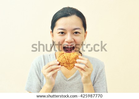 Happy woman holding and eating fries chicken, vintage tone image - stock photo