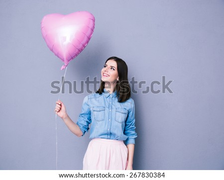 Happy woman holding balloon over gray background. Lookign away.  - stock photo