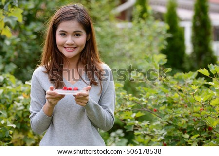 Happy woman holding berries in her hand