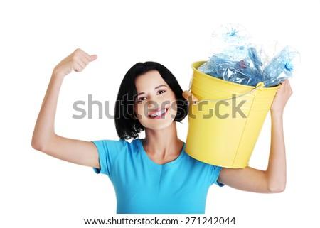 Happy woman holding bucket of plastic rubbish. - stock photo