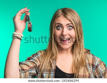 Happy woman holding car keys on a green background - stock photo