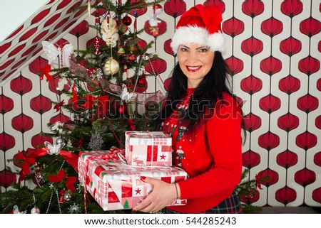 Happy woman holding Christmas gifts and standing near tree