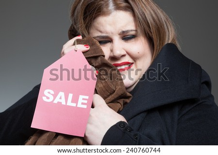 Happy woman holding clothes on sales.