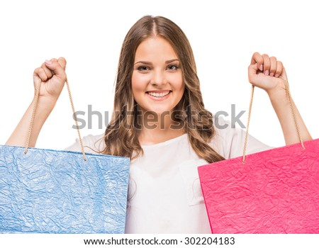 Happy woman holding colored shopping bags in two hands on white background.