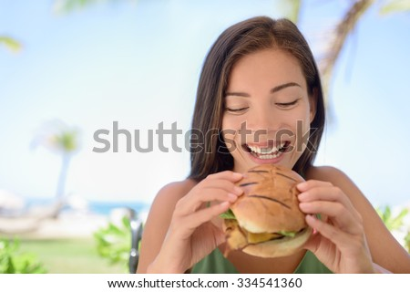 Happy woman holding eating fresh burger sandwich at beach. Young female is sitting at outdoor restaurant. Beautiful tourist is having fresh burger during summer vacation holidays. - stock photo