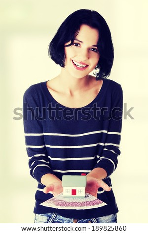 Happy woman holding euros bills and house model - real estate loan concept - stock photo