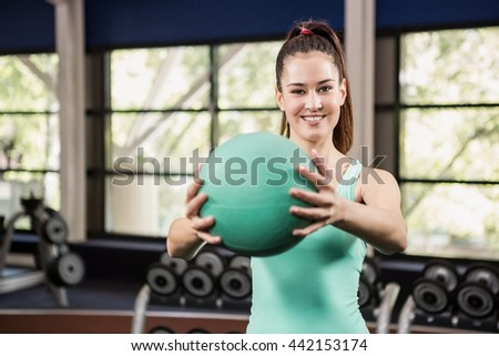 Happy woman holding exercise ball at gym - stock photo