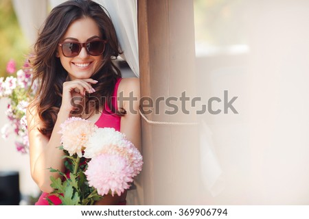 Happy woman holding flowers. woman with flowers walking in the city street. Closeup portrait of cute young girl with bunch of flowers smiling outdoors. Young woman with flowers  - stock photo