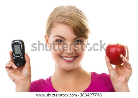 Happy woman holding glucose meter and fresh ripe apple, concept of diabetes, checking sugar level - stock photo