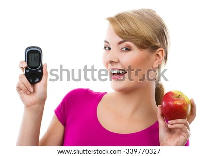 Happy woman holding glucose meter with positive result of measurement sugar level and fresh ripe apple, concept of diabetes, checking sugar level, white background