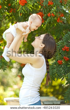 Happy woman holding in arm a laughing baby in a garden