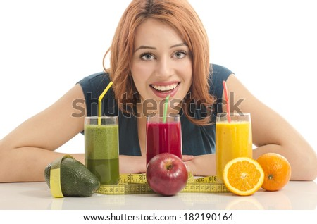Happy woman holding in front of her three different smoothie. Cheerful young woman eating healthy salad, fruits , orange juice and green smoothie - stock photo