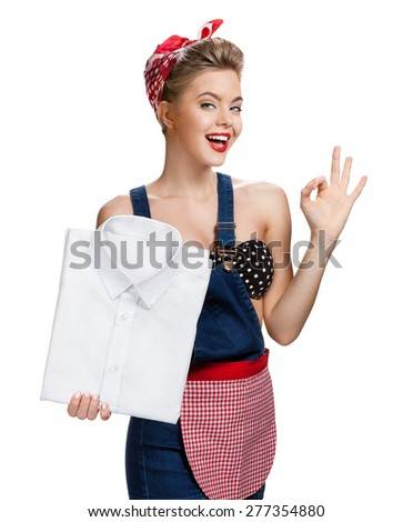 Happy woman holding laundered white shirt and showing us it's Okay / young beautiful American pin-up girl isolated on white background. Cleaning service concept - stock photo