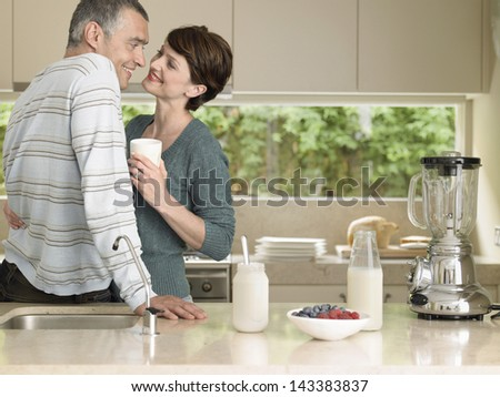 Happy woman holding milkshake while looking at husband at kitchen counter