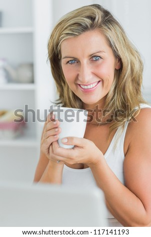 Happy woman holding mug in the kitchen