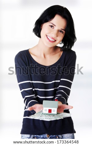 Happy woman holding polish zloty bills and house model over white - real estate loan concept  - stock photo