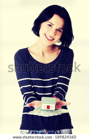 Happy woman holding polish zloty bills and house model - real estate loan concept - stock photo