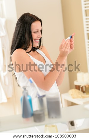 Happy woman holding positive pregnancy test in bathroom