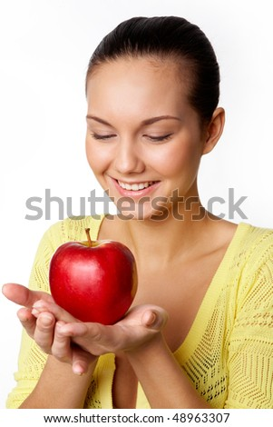 Happy woman holding red apple on palm and looking at it with smile over white background