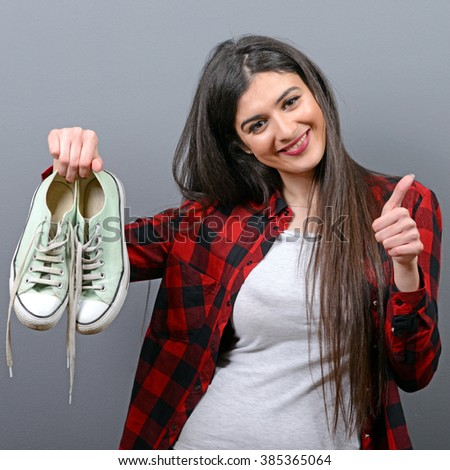 Happy woman holding retro sneakers against gray background - stock photo