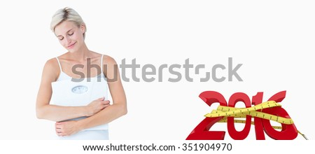 Happy woman holding scales against white background with vignette - stock photo