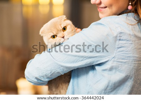 happy woman holding scottish fold cat at home - stock photo