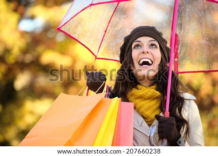 Happy woman holding shopping bags and umbrella under autumn rain. Brunette fashion female shopper outside in fall season. - stock photo