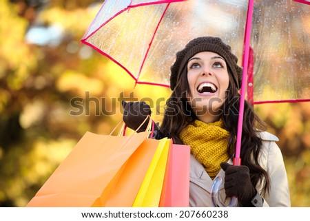 Happy woman holding shopping bags and umbrella under autumn rain. Brunette fashion female shopper outside in fall season. - stock photo