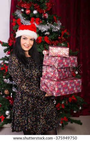 Happy woman holding stack of Christmas gifts  and standing in front of tree - stock photo
