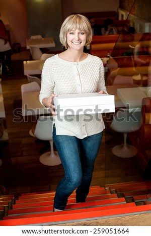 Happy woman holding stack of pizza boxes - stock photo
