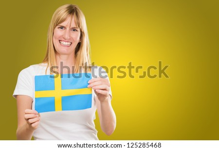 Happy Woman Holding Swedish Flag against a yellow background - stock photo