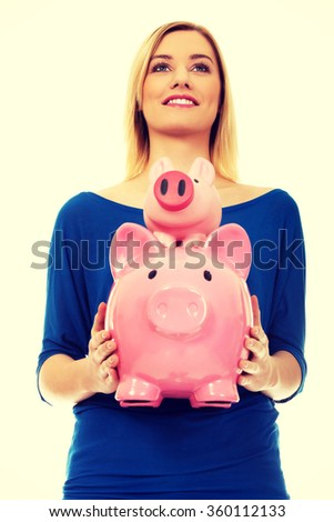 Happy woman holding two piggybanks.