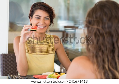 Happy Woman Holding Watermelon Slice In Front Of Female Friend  - stock photo