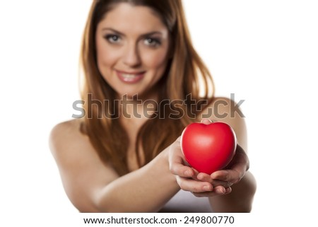 happy woman holds in her hand a heart shape object - stock photo