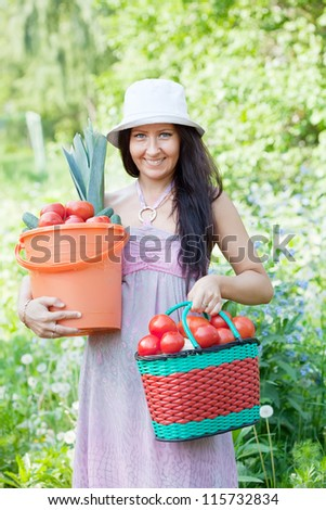 Happy woman holds vegetables harvest in summer garden - stock photo