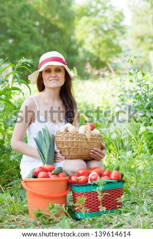Happy woman holds vegetables harvest in summer garden