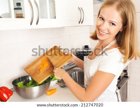 happy woman housewife preparing vegetable salad in the kitchen - stock photo