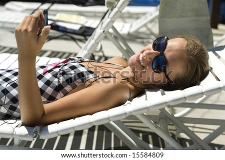 Happy woman in a bathing-suit laying by the pool, listening to music. - stock photo
