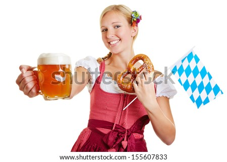 Happy woman in a dirndl holding beer, pretzel and a bavarian flag