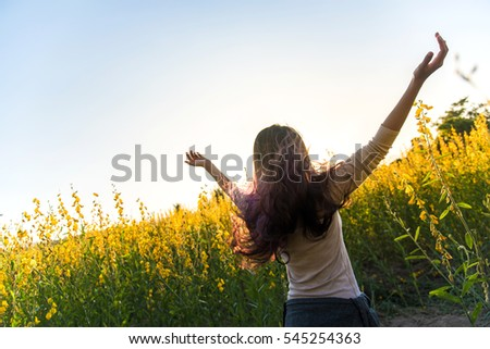 Happy woman in a field of yellow flowers,Crotalaria.