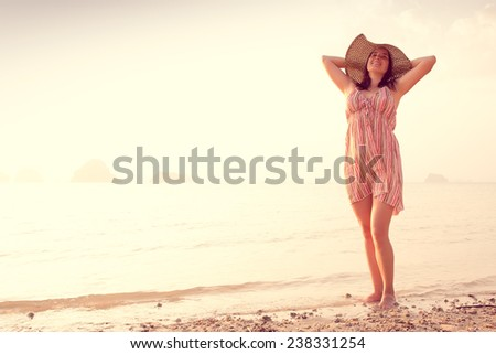 Happy Woman in a hat and short dress enjoys in Sea Sunset. In the background hilly karst mountains to the sea,  vintage color - stock photo