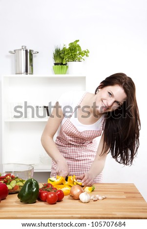 happy woman in a kitchen cutting yellow paprika for salad - stock photo
