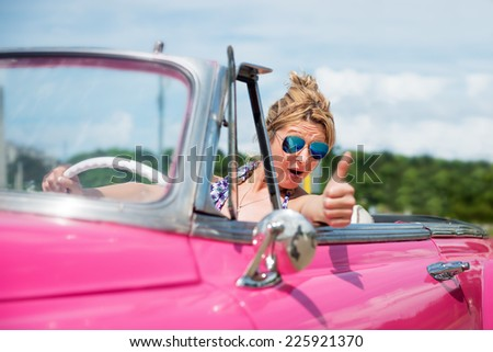 Happy woman in a pink convertible car, cabriolet, looking at camera, thumb up - stock photo