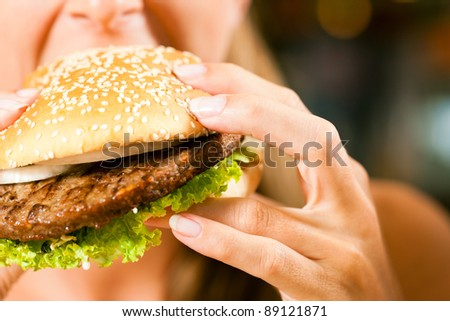 Happy woman in a restaurant eating a fast food hamburger, focus on the burger - stock photo