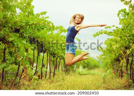 Happy woman in a vineyard is jumping and having fun during the harvest season. Fresh ripe grapes on a vine at the background. Eco lifestyle concept. - stock photo