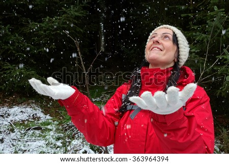 happy woman in a winter forest with falling snow. Landscape. - stock photo